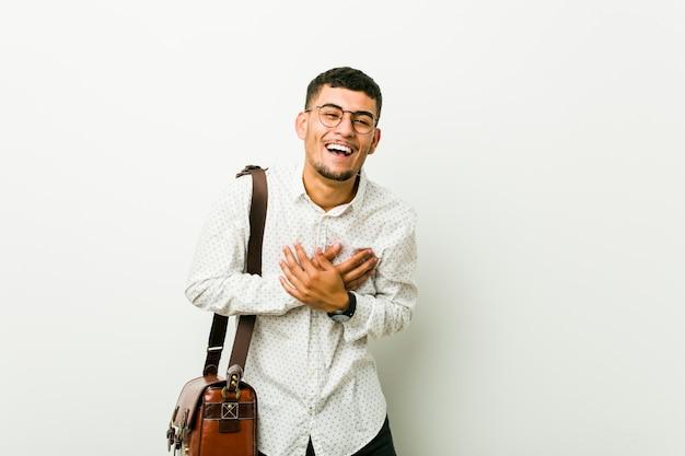 Homem de negócio ocasional latino-americano novo que ri mantendo as mãos no coração, conceito da felicidade. Foto Premium