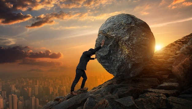 Homem de negócio que empurra a grande pedra até o monte, tarefas pesadas do negócio e conceito dos problemas. Foto Premium