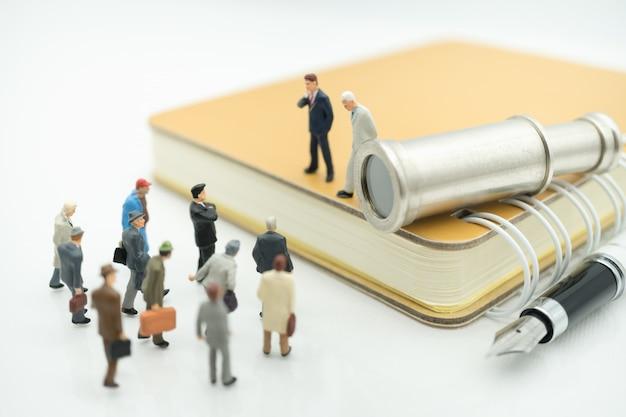 Homem de negócio que está no livro com binóculos usando-se como o conceito do recruta do trabalho do negócio. Foto Premium