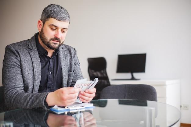 Homem de negócio que senta-se na mesa e no contrato de assinatura. Foto Premium