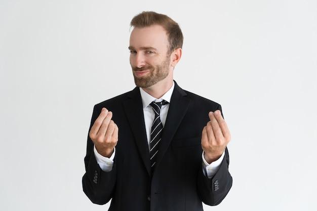 Homem de negócio sneaky que mostra o gesto do dinheiro, pedindo o dinheiro e olhando a câmera. Foto gratuita