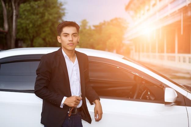 Homem de negócios adulto masculino em um terno e segurando uma chave do carro em sua mão. carros brancos ao fundo Foto Premium