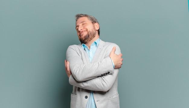 Homem de negócios adulto se sentindo apaixonado, sorrindo, acariciando e abraçando a si mesmo, permanecendo solteiro, sendo egoísta e egocêntrico Foto Premium