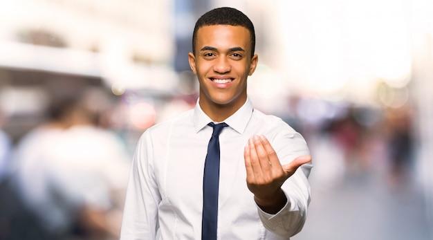 Homem de negócios afro-americano novo que convida para vir com mão. feliz que você veio na cidade Foto Premium