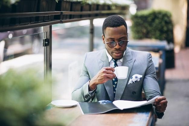 Homem de negócios americano africano bebendo café Foto gratuita