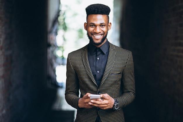 Homem de negócios americano africano com telefone Foto gratuita