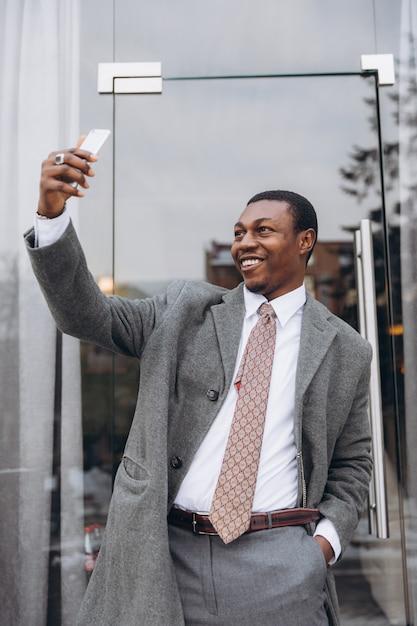Homem de negócios americano africano no clássico terno cinza segurando um smartphone e fazer selfie. Foto Premium
