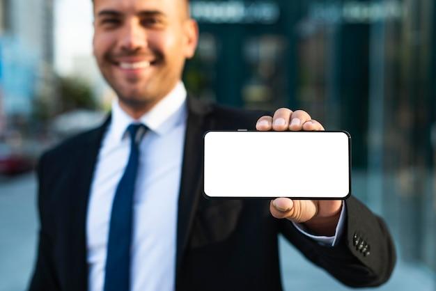 Homem de negócios ao ar livre mostrando um telefone de cópia espacial Foto gratuita