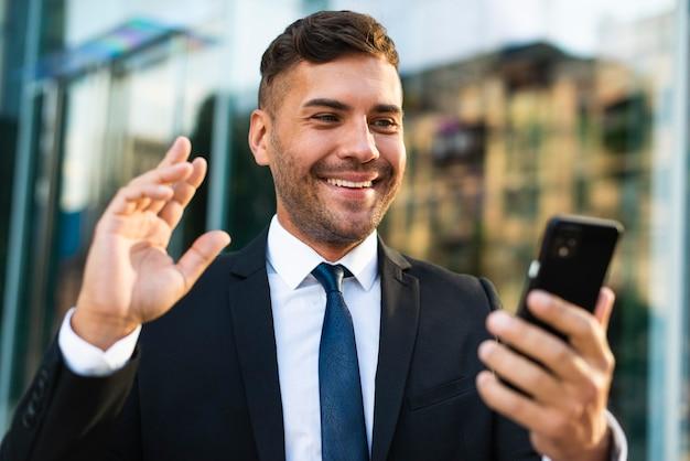 Homem de negócios ao ar livre segurando o telefone e sorrindo Foto gratuita