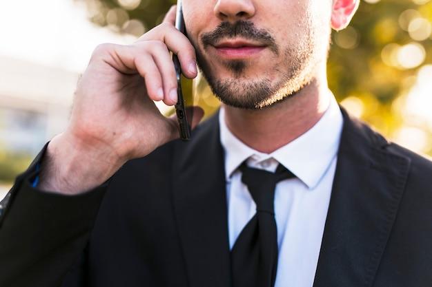 Homem de negócios ao telefone no parque Foto gratuita