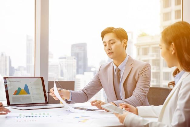 Homem de negócios asiático na reunião no escritório da cidade Foto Premium