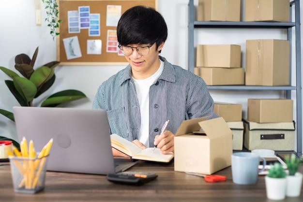Homem de negócios asiático, preparando uma caixa de entrega Foto Premium