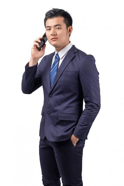 Homem de negócios asiático que usa o smartphone com isolado no fundo branco. Foto Premium