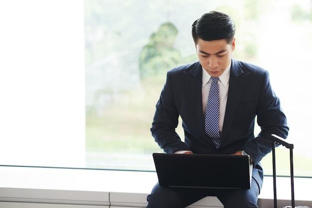 Homem de negócios asiático sentado no peitoril da janela, com mala mostrando e trabalhando no laptop Foto gratuita