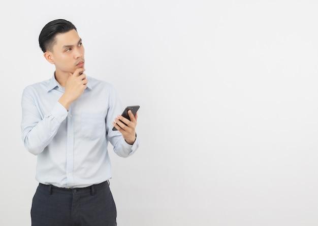 Homem de negócios asiáticos bonito jovem segurando um smartphone preto e pensando em uma idéia enquanto olha para cima Foto Premium
