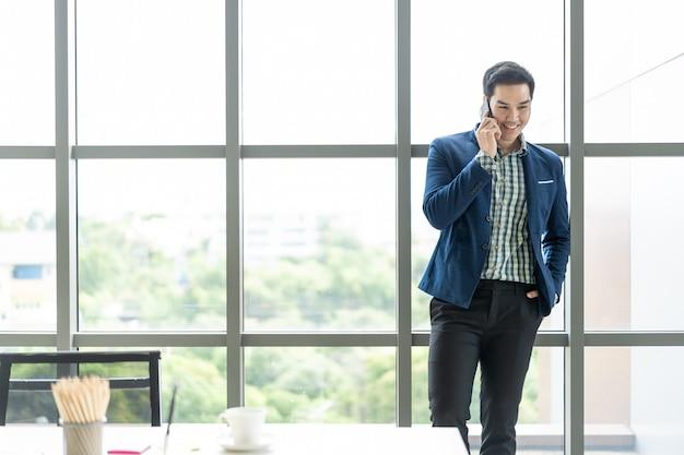 Homem de negócios asiáticos inteligente falando usando um smartphone. Foto Premium