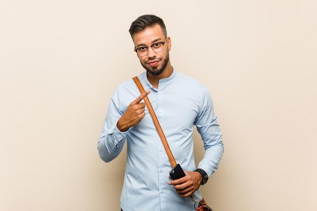 Homem de negócios asiáticos jovens de raça mista, segurando um telefone apontando com o dedo para você, como se convidando se aproximar. Foto Premium