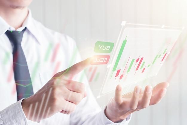Homem de negócios asiáticos usando o dedo tocar no botão vender na tela virtual digital com gráfico de castiçal, financeira e conceito de investimento Foto Premium