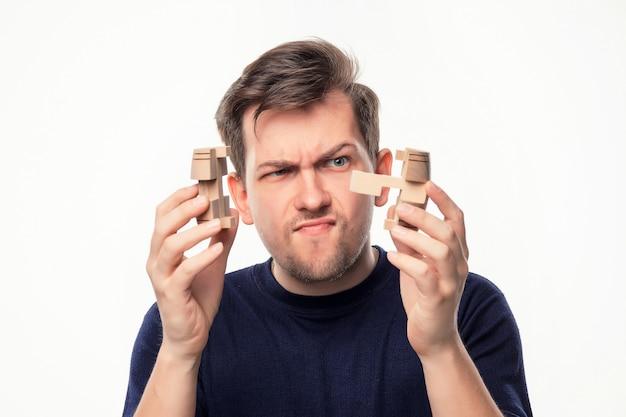 Homem de negócios atraente 25 anos olhando confuso com quebra-cabeças de madeira. Foto gratuita