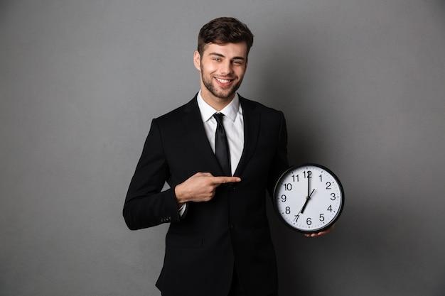 Homem de negócios atraente em terno preto clássico, apontando com o dedo no grande relógio Foto gratuita