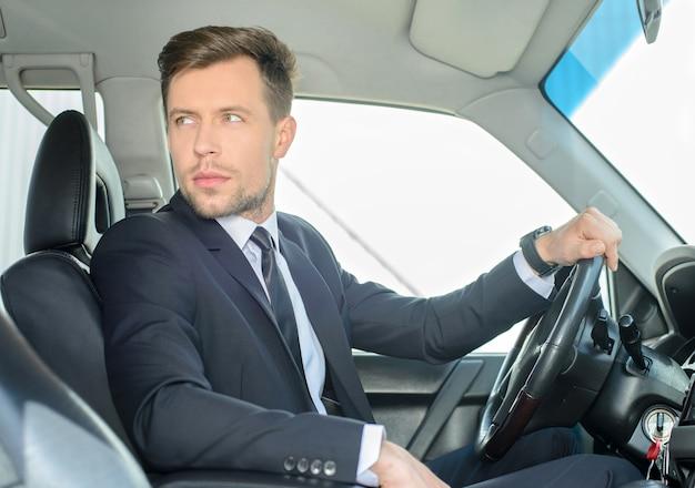 Homem de negócios bem sucedido novo que monta no carro. Foto Premium