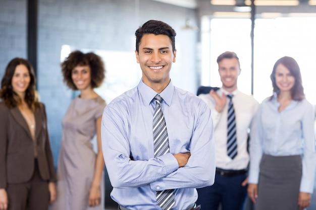 Homem de negócios bem sucedido, sorrindo com os braços cruzados e seus colegas posando Foto Premium