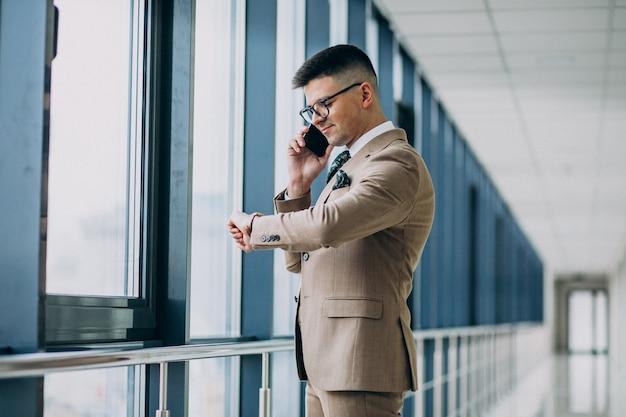 Homem de negócios bonito jovem de pé com telefone no escritório Foto gratuita