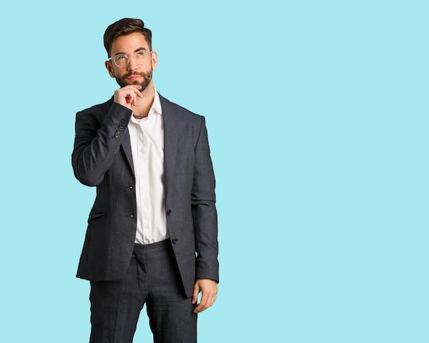 Homem de negócios bonito jovem duvidando e confuso Foto Premium