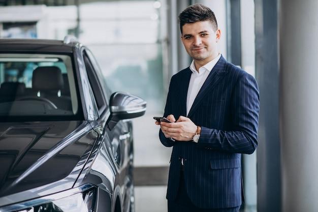 Homem de negócios bonito jovem em uma sala de exposições de carro, escolhendo um carro Foto gratuita