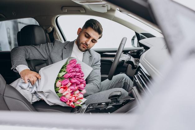 Homem de negócios bonito jovem entregando buquê de flores lindas Foto gratuita