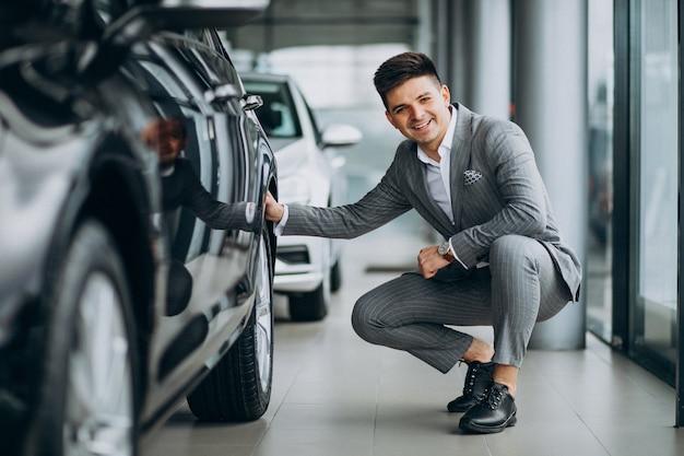 Homem de negócios bonito jovem escolhendo um carro em uma sala de exposições de carros Foto gratuita