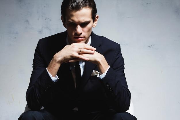 Homem de negócios bonito jovem terno preto senta-se na cadeira na parede cinza Foto Premium