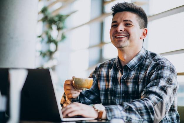 Homem de negócios bonito jovem usando laptop em um café Foto gratuita