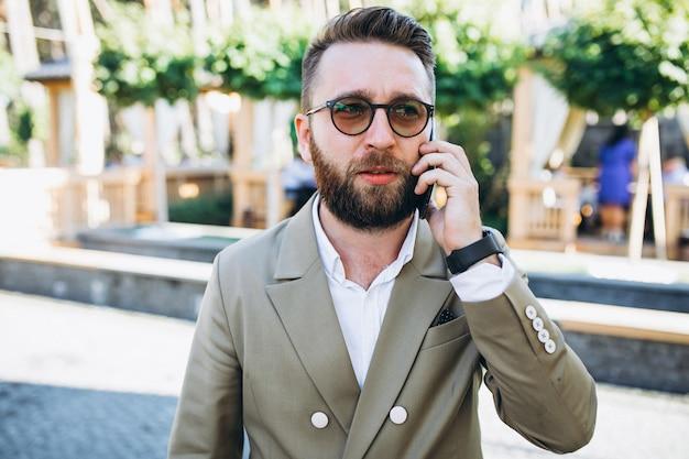 Homem de negócios bonito jovem usando telefone Foto gratuita