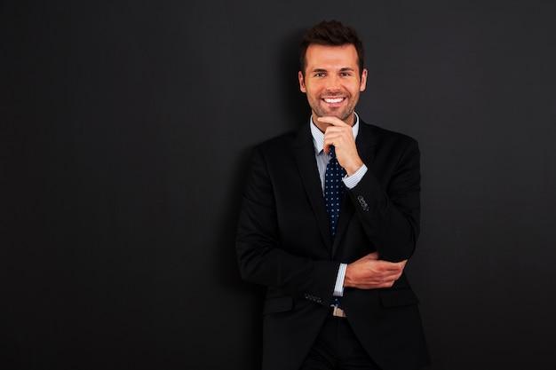 Homem de negócios bonito parado na lousa Foto gratuita