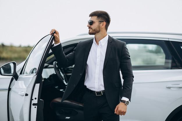 Homem de negócios bonito pelo carro branco Foto gratuita