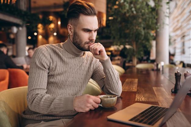 Homem de negócios bonito trabalhando no computador e tomando café em um café Foto gratuita