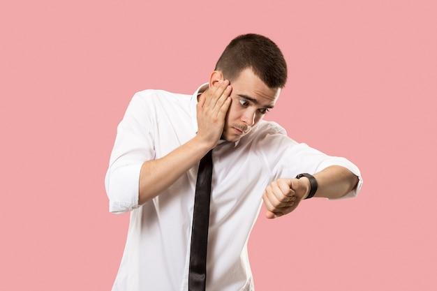 Homem de negócios bonito verificando seu relógio de pulso isolado em rosa. uau. retrato de homem atraente com metade do corpo Foto gratuita