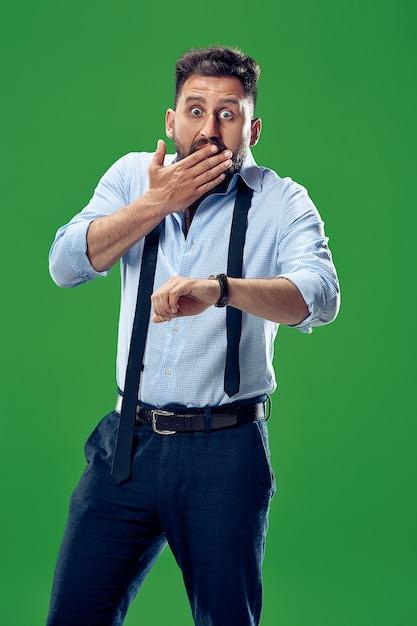 Homem de negócios bonito verificando seu relógio de pulso isolado em verde. uau. retrato de homem atraente com metade do corpo Foto gratuita