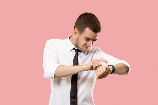 Homem de negócios bonito verificando seu relógio de pulso isolado na parede rosa Foto gratuita