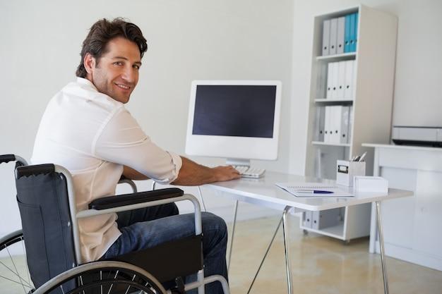 Homem de negócios casual em cadeira de rodas, trabalhando em sua mesa Foto Premium