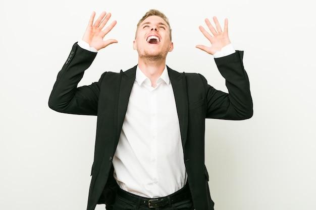 Homem de negócios caucasiano jovem gritando para o céu, olhando para cima, frustrado. Foto Premium