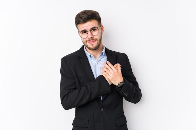 Homem de negócios caucasiano jovem posando em uma parede branca isolada homem de negócios caucasiano jovem tem expressão amigável, pressionando a palma da mão no peito. conceito de amor Foto Premium