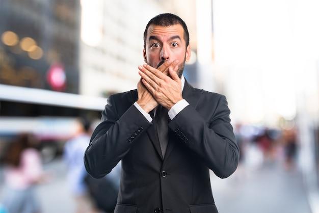 Homem de negócios cobrindo a boca em fundo não focado Foto Premium