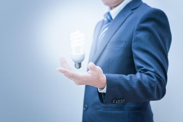 Homem de negócios com a mão vazia. mão segurando uma luz Foto Premium