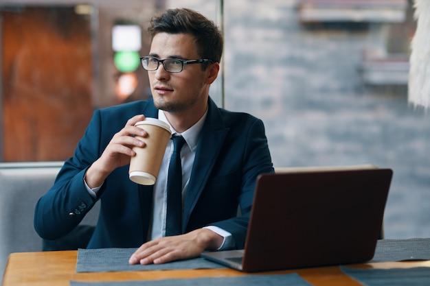 Homem de negócios com café com o laptop na mesa Foto Premium