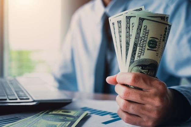 Homem de negócios com dinheiro à disposição, dólar americano, investimento, sucesso e conceitos de negócio rentável. Foto Premium
