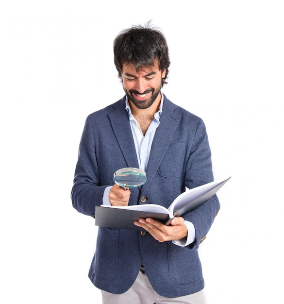 Homem de negócios com lupa redingando um livro sobre fundo branco Foto gratuita