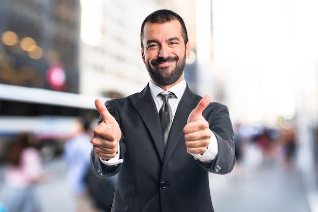 Homem de negócios com o polegar acima em fundo não focado Foto Premium