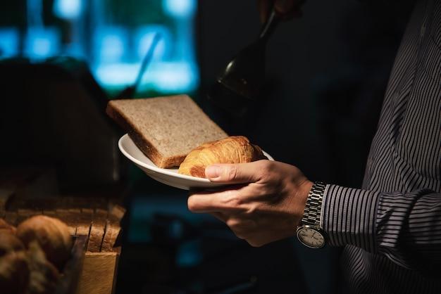 Homem de negócios comer o café da manhã americano situado num hotel Foto gratuita